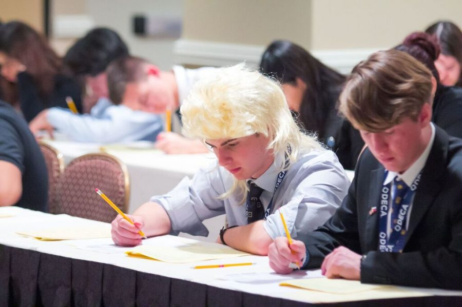 Two students take a test on concepts taught at DECA practices.