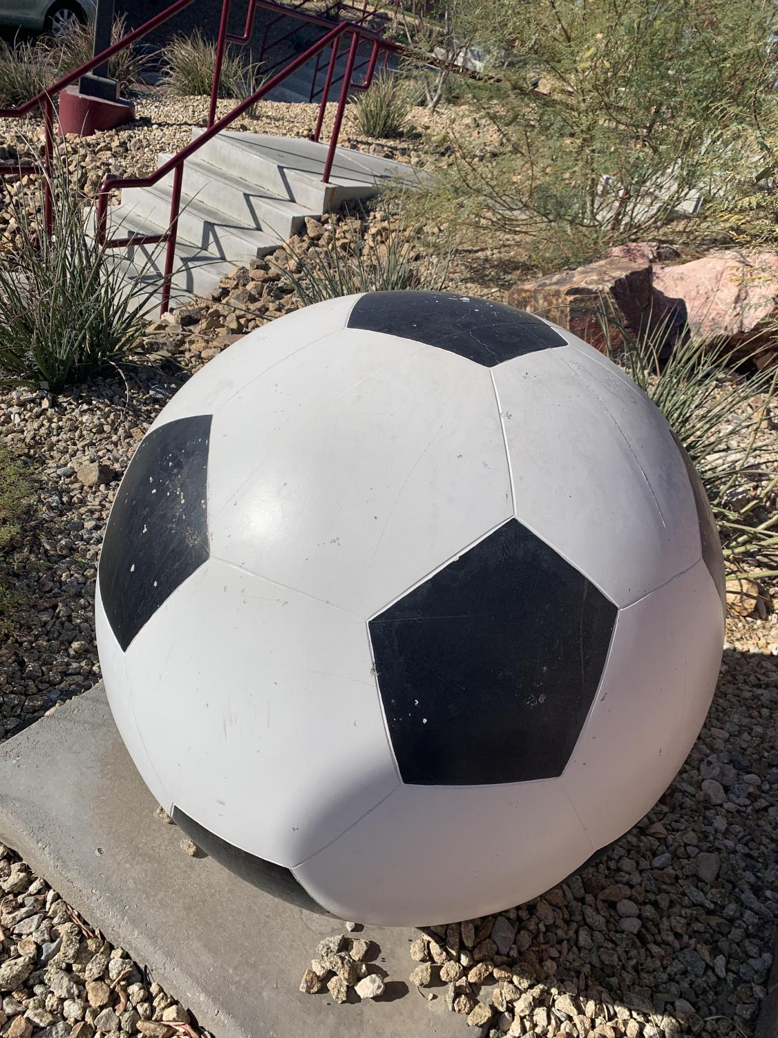 Soccer ball right outside the soccer field!